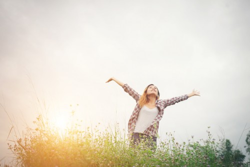 Young beautiful hipster woman in a flower field at sunset. Freedom enjoying with nature.